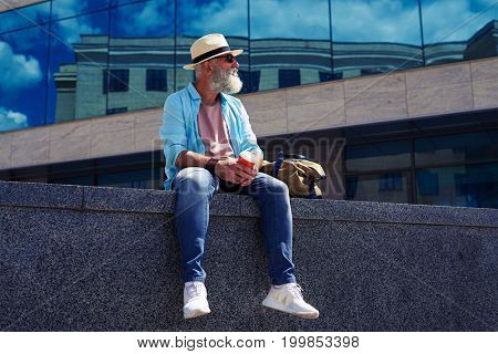 Wide shot of satisfied male enjoying city while drinking coffee and sitting under skyscraper