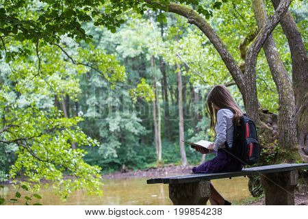 Pretty Little Blonde Schoolgirl With Backpack Sitting On The Bench In The Nature Park Near Lake And