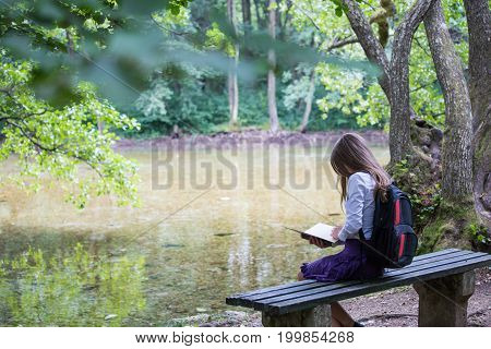 Pretty Little Blonde Schoolgirl With Backpack Sitting On The Bench In The Park Near Lake And Reading