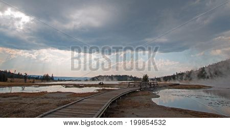 Boardwalk curving between Hot Lake hot spring and Hot Cascades hot spring in the Lower Geyser Basin in Yellowstone National Park in Wyoming United States