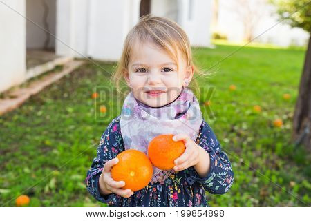 Happy laughing child playing with orange in a garden