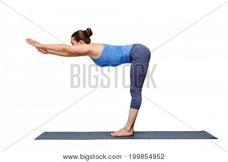 Woman doing yoga in standing forward bend pose transition to uttanasana on yoga mat isolated on white