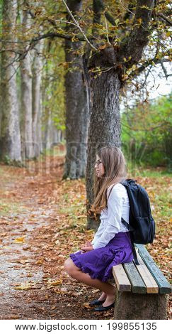 Pretty Beautiful Blonde Child Schoolgirl Back To School Sitting On Bench In Tree Alley In Nature Wit
