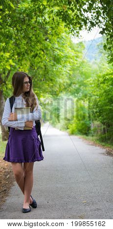 Pretty Beautiful Blonde Child Schoolgirl Back To School Standing In Tree Alley In Nature Holding Not