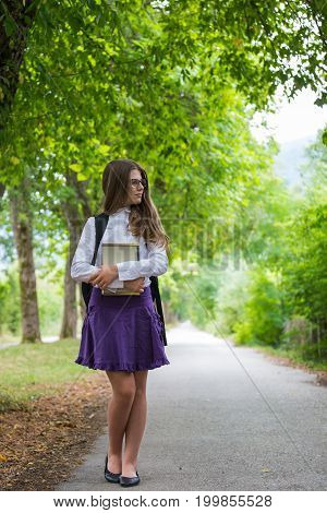 Pretty Beautiful Blonde Child Schoolgirl Enjoying Back To School Walking Through Tree Alley In Natur