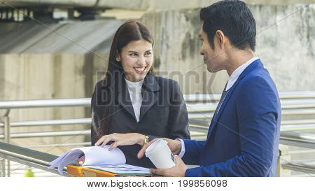 the business people of man and woman talk together about the presentation work on paper sheet in feeling happy at the outdoor space in the morning.
