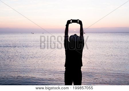 man taking photos of sunset with mobile phone