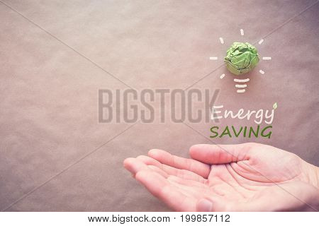 Green paper light bulb with Energy saving over hands eco energy saving concept