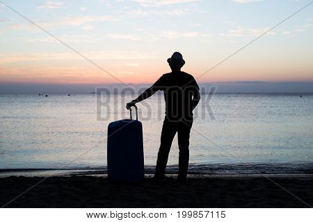 Back view silhouette of man standing with suitcase on blue sea outdoors background. Arriving at destination.