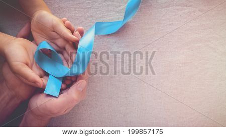 Adult and child hands holding Light blue sky blue ribbons toning background Prostate Cancer Awareness and Adrenocortical carcinoma awareness