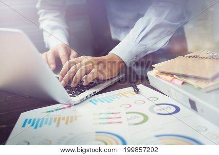 double exposure of businessman hand working laptop on wooden desk in office in morning light. The concept of modern work with advanced technology. vintage effect