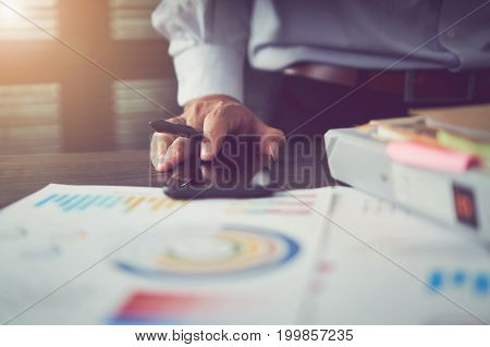 Businessmen point their finger at financial charts to demonstrate the company's past performance. Business Concepts by Functionality. vintage effect.