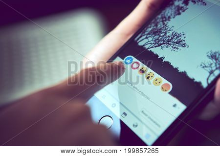 Bangkok, Thailand - August 16, 2017 : hand is pressing the Facebook screen on apple iphone6 Social media are using for information sharing and networking.