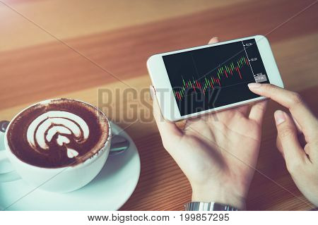 The woman holds the phone on a table with a graphical screen to invest the stock's value. Investment concepts that rely on decision-making information vintage effect.