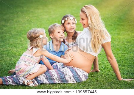 Cute young pregnant mother sitting on fresh green grass field with her three kids, children are looking forward to the birth of a brother or sister, happy big family