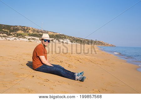 a man sitting on the beach in pants and a brown t-shirt, watching the sea.