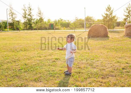 Portrait of cute little baby boy having fun outside. Smiling happy child playing outdoors.
