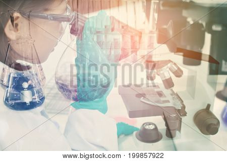Double exposure of girl using microscope scientific experiment in the laboratory