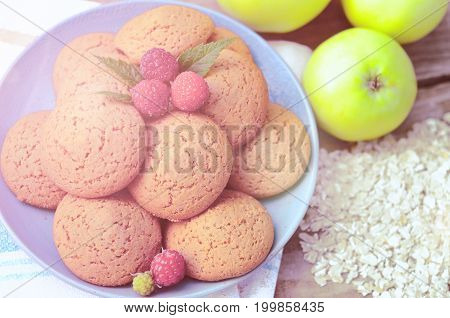 Oatmeal cookies with berry raspberries in a Cup of the green apples next to a bunch of flakes oatmeal ha a wooden Board with soft light