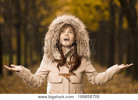 Woman in autumn coat with open arms enjoying the rain