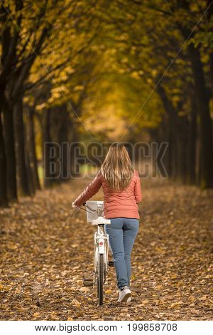 Woman walking with bike in Autumn park