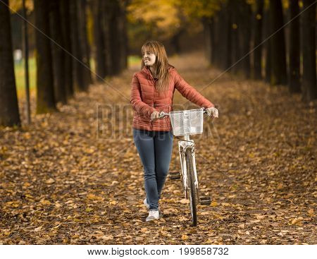 Woman on bike in Autumn park