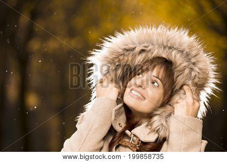 Smiling woman in autumn coat enjoying the rainin