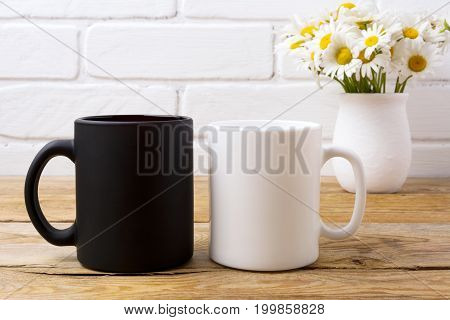 White And Black Mug Mockup With Chamomile Bouquet In Rustic Vase