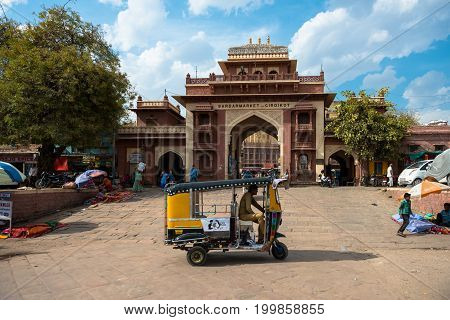 JODHPUR RAJASTHAN INDIA - MARCH 04 2016: Wide angle picture of tuk tuk and Girdikot Gate in Jodhpur the blue city of Rajasthan in India.