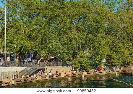 Zurich, Switzerland - 20 July, 2016: people on the embankment of Lake Zurich in the city of Zurich. Zurich is the largest city in Switzerland and the capital of the Swiss canton of Zurich, Lake Zurich is a lake extending southeast of the city.