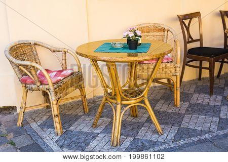 Old fashioned cafe terrace. Tables and wicker chairs in a cafe.