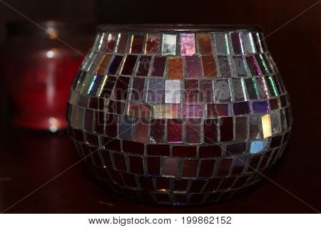 A multi colored glass candle holder on a cabinet