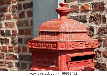 Belgian red postbox on the street near old brick wall.