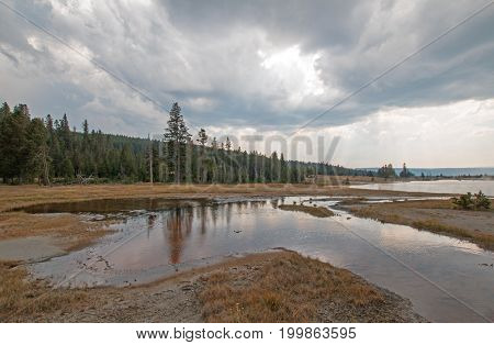 Tangled Creek emptying into Hot Lake hot spring under cumulus clouds in the Lower Geyser Basin in Yellowstone National Park in Wyoming United States