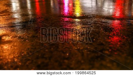 Water on street and color lighting traffic night illuminated reflection liquid using the car on the road when it weather rainy season accident brake at modern city.