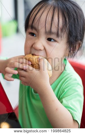 Asian Little Chinese Girl Eating Bread