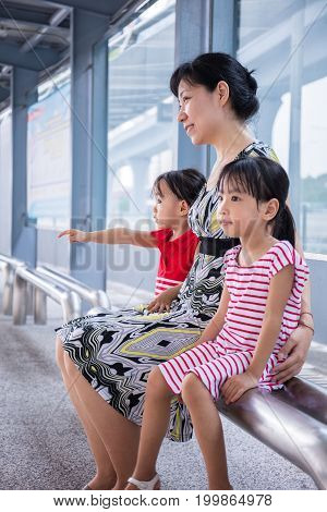 Asian Chinese Mother And Daughters Waiting For A Bus