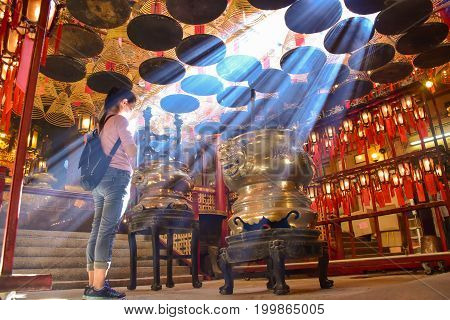 Hong Kong-June 10 2017: asian women prays at Man Mo Temple in Hong Kong with lamps and incense coils hang on the ceiling free access for everyone
