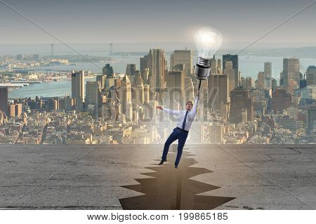 Businessman flying over gap on light bulb balloon