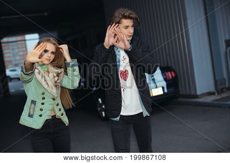 Couple hiding faces from paparazzi outdoors at parking. Fashion young couple in rock style. Pretty girl and handsome man shielding their faces from photographers