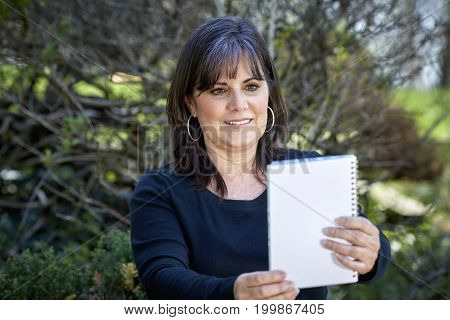 Middle Aged Woman Reading A Notebook