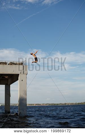 A man is jumping into the sea from a high pier. Adrenaline and extreme. Back somersault in the jump.