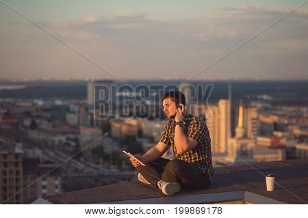 A hipster guy listens to music on headphones on the roof of a high-rise building. Freelancer in search of inspiration.