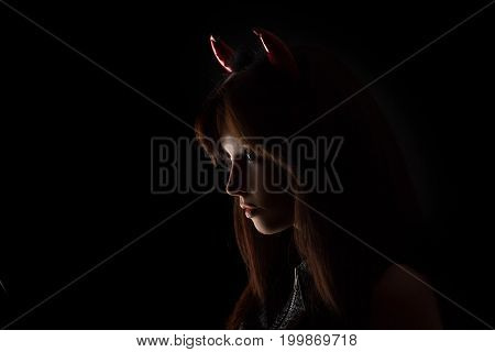 Sexy brunette girl wearing a halloween costume of a devil. Beautiful mixed race Caucasian Asian young girl posing against black background in studio. Silhouette portrait.