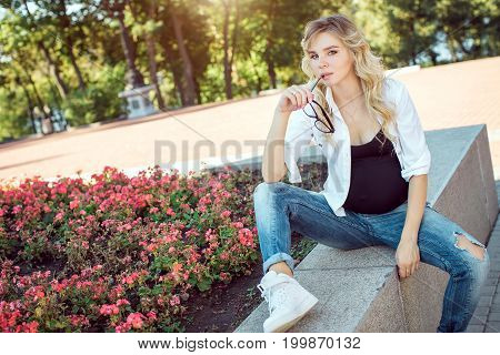 Portrait of happy young pregnant model sitting outdoors in the park. Future mom expecting baby. Copy space