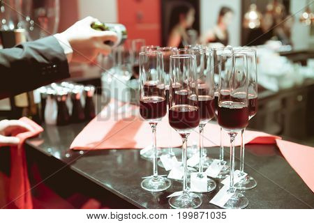 Waiter Pouring Sweet Wine In Wine Glass On Bar For Service In Luxury Dinner Party, Blurry Background