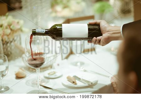 Waiter Pouring Red Wine In Wine Glass On The Table For Service In Luxury Dinner Party, Blurry Backgr