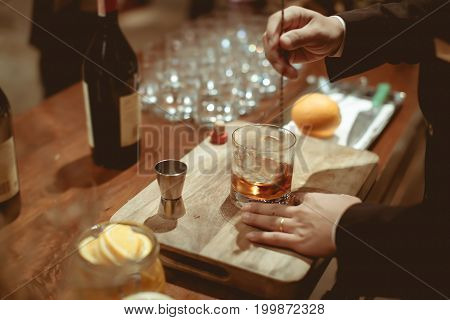 Bartender Is Stirring Cocktails  On Chopping Wood And Counter Bar In Luxury Dinner Party, Blurry Bac