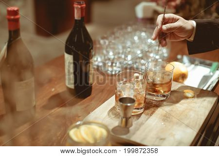 Bartender Is Stirring Cocktails  On Chopping Wood And Counter Bar On In Luxury Dinner Party, Blurry