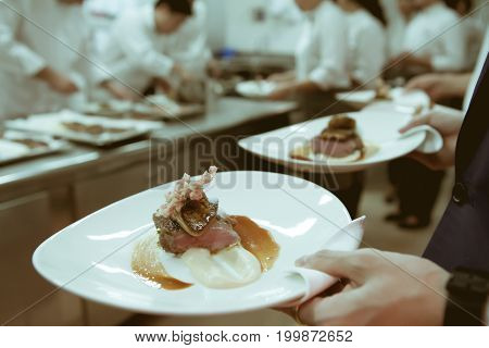 Waiter Serving Food In Luxury Dinner Party, Blurry Background With Vintage Color Style.
